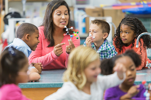 An Hispanic woman in her 40s teaching a multi-ethnic group of elementary school students in science lab. She is holding a model of a molecule and talking while the curious children watch and listen.
