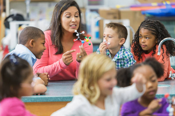 Multiracial teacher and children in science lab An Hispanic woman in her 40s teaching a multi-ethnic group of elementary school students in science lab. She is holding a model of a molecule and talking while the curious children watch and listen. elementary age stock pictures, royalty-free photos & images