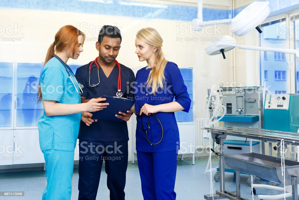 Multiracial team of doctors discussing a patient standing in a operating room stock photo