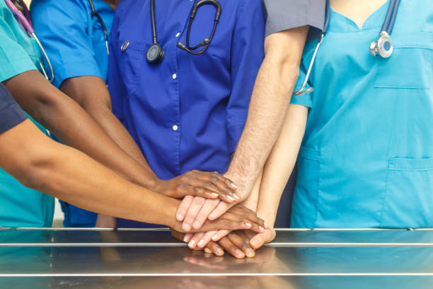Multiracial team of young doctors stacking hands indoor, Group Of Multiracial Doctor surgery team stacking hands in a operating room, medical teamwork stock photo