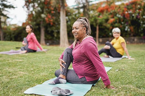 Multiracial women doing yoga exercise with social distance for coronavirus outbreak at park outdoor - Healthy lifestyle and sport concept