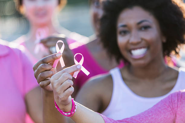multiracial women holding breast cancer awareness ribbon - breast cancer awareness 個照片及圖片檔