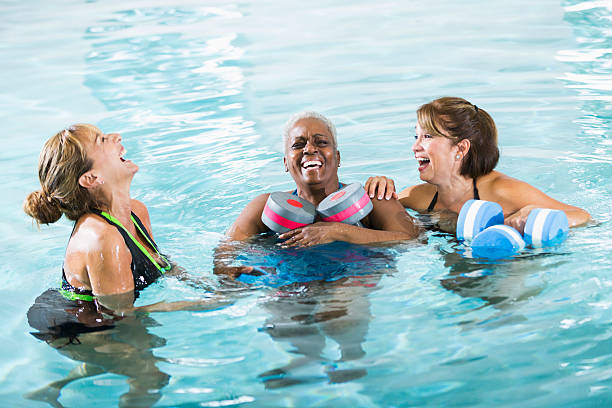 Multirazziale donna in acqua esercizio classe Ridere - foto stock