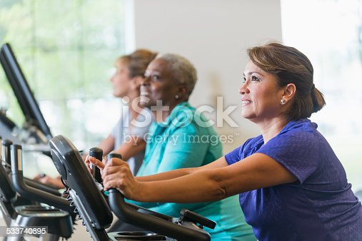 Multi-ethnic women at the gym, on exercise bikes.  Focus on mature Hispanic woman (50s) in foreground.