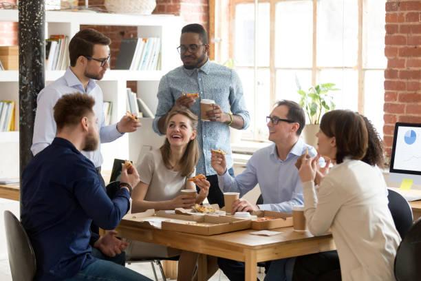 multiracial arbetslag äter pizza tillsammans på rast - lunchrast bildbanksfoton och bilder