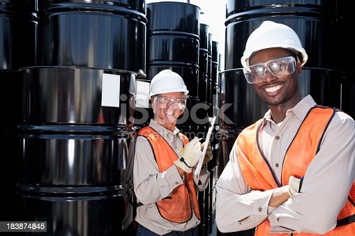 Senior man, 60s, with young African American co-worker, 20s, taking inventory by steel drums.  Focus on man with clipboard.