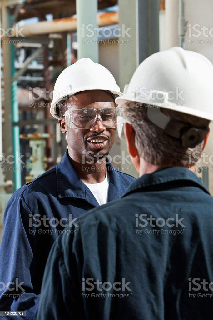 Multiracial workers at industrial plant talking stock photo