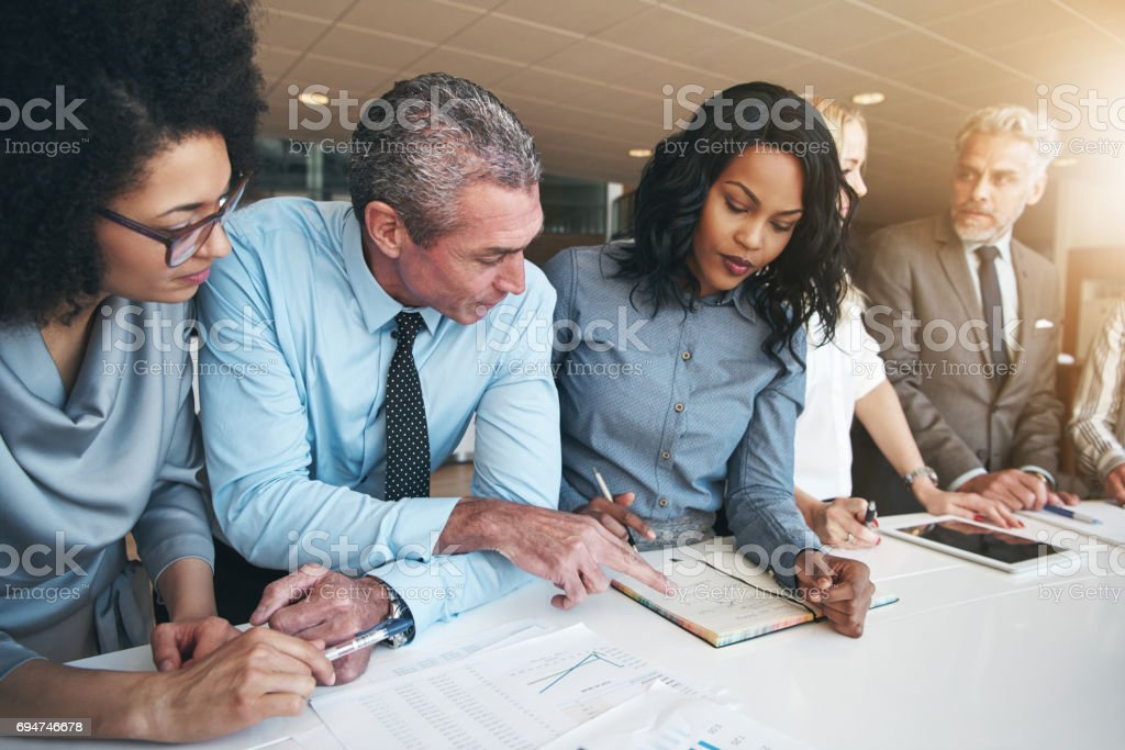 Multiracial workers discussing papers sitting in office stock photo
