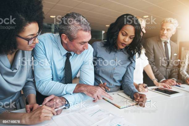 Multiracial Workers Discussing Papers Sitting In Office Stock Photo - Download Image Now