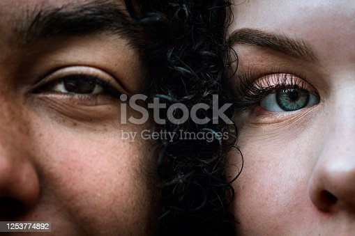 A close up photo of a teenage African America man and a Caucasian woman face to face.