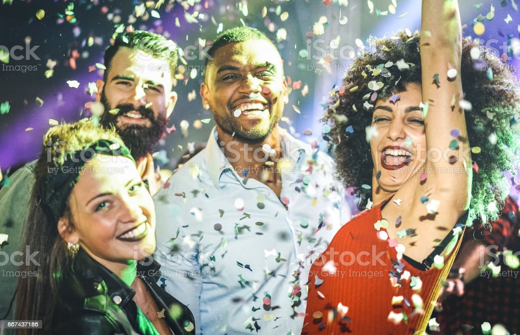 Multiracial young friends dancing at night club under confetti rain - Happy people having crazy fun at nightclub after party - Nightlife drunk concept with guys and girls celebrate at concert festival stock photo