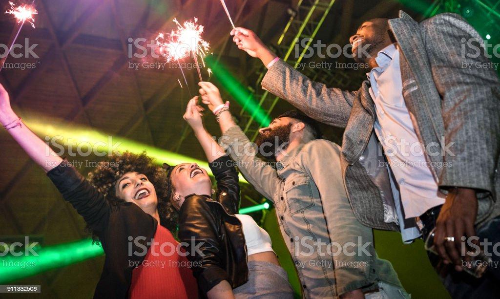 Multiraciales jeunes amis danser à la discothèque avec concept ivre de Cierge magique feu d'artifice - Happy people s'amusant fou dans la discothèque après la fête - vie nocturne avec les gars et les filles au concert événement festival - Photo