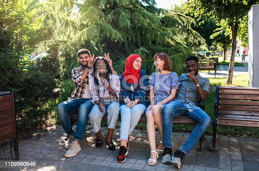 istock Multiracial young friends sitting by the street and having fun. 1159990946