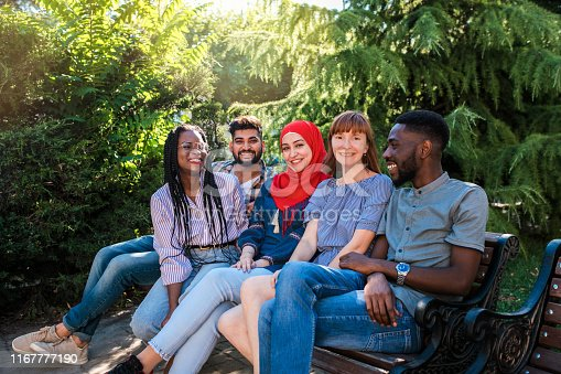 istock Multiracial young friends sitting by the street and having fun. 1167777190
