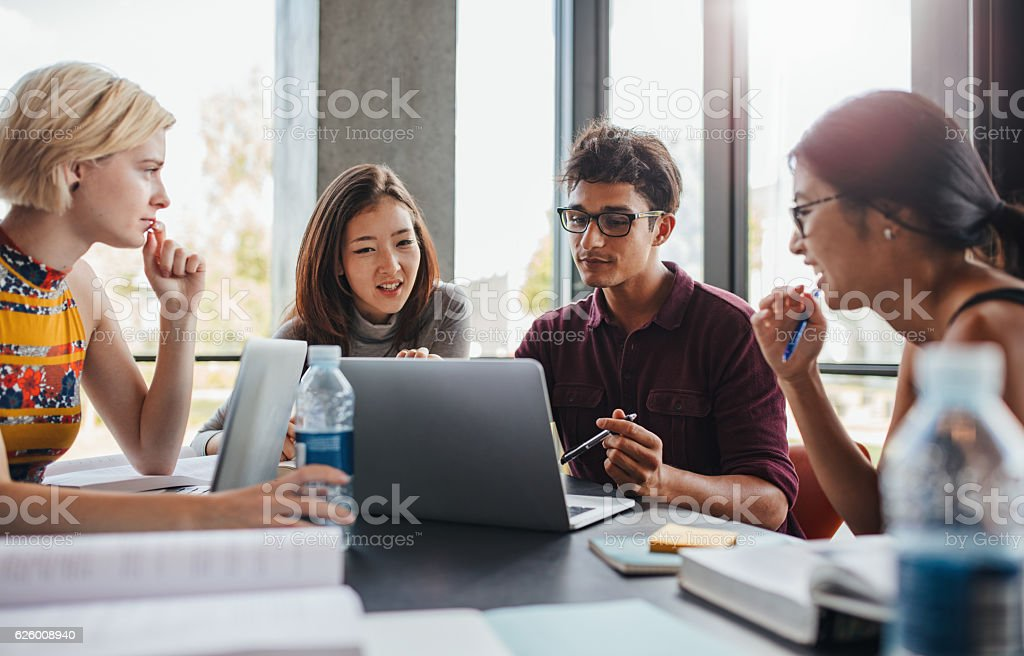 Multiracial young people doing group study at library stock photo