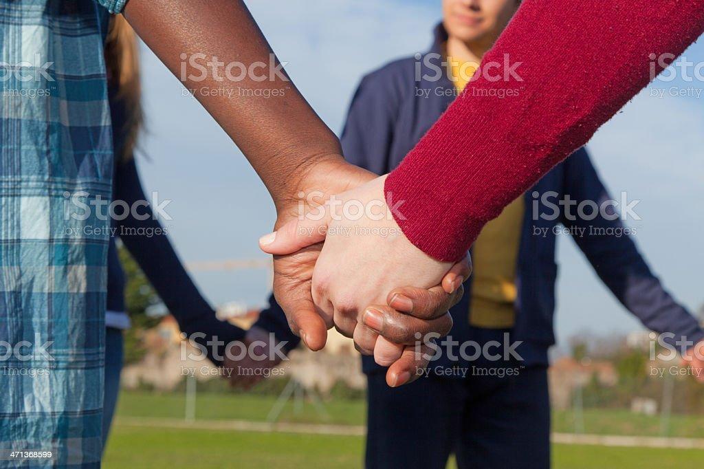 Jeunes multiraciales tenant les mains dans un cercle - Photo