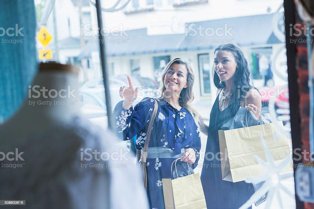 Multi-racial young women window shopping stock photo