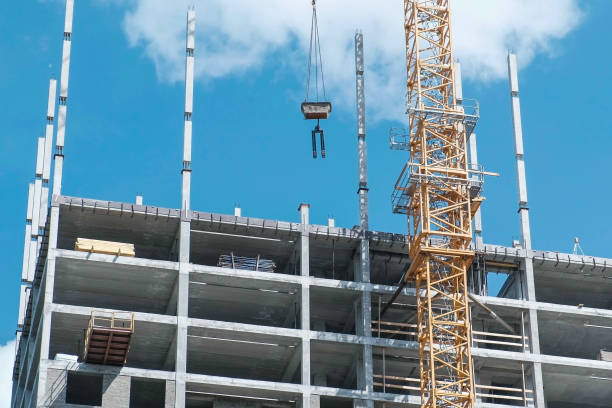 Multi-storey under construction appartment building with a working building crane on a sky background. Multi-storey under construction appartment building with a building crane on a sky background. brics stock pictures, royalty-free photos & images
