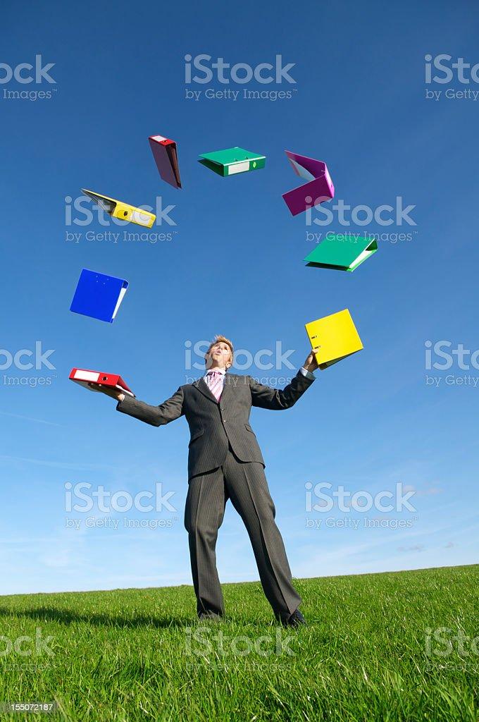 Multitasking Businessman Juggling File Folder Binders in Empty Meadow royalty-free stock photo