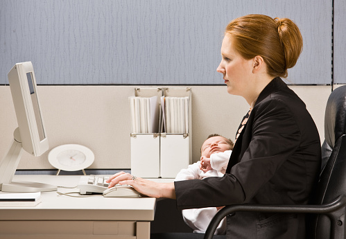 Multitasking Businesswoman Holding Baby At Work Stock Photo - Download Image Now