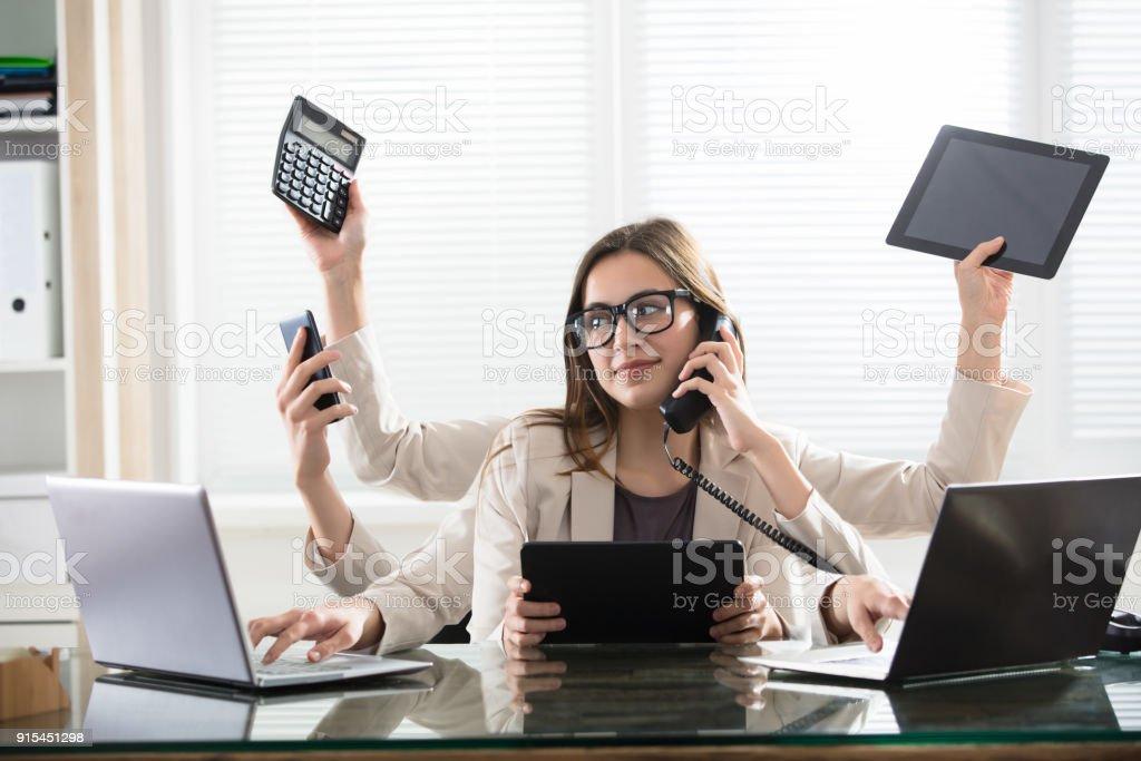 Multitasking Businesswoman In Office stock photo