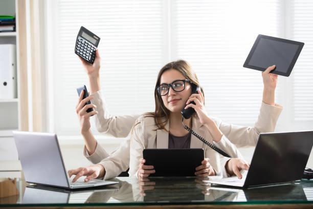 multitasking zakenvrouw in office - druk stockfoto's en -beelden