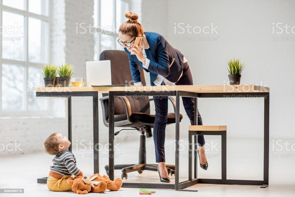 Multitasking-Geschäftsfrau mit ihrem Sohn im Büro – Foto
