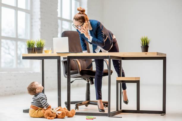 femme d'affaires de multitâche avec son fils au bureau - femmes actives photos et images de collection