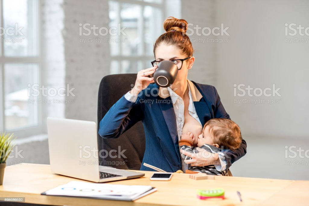 Multitasking businesswoman with her son working at the office stock photo