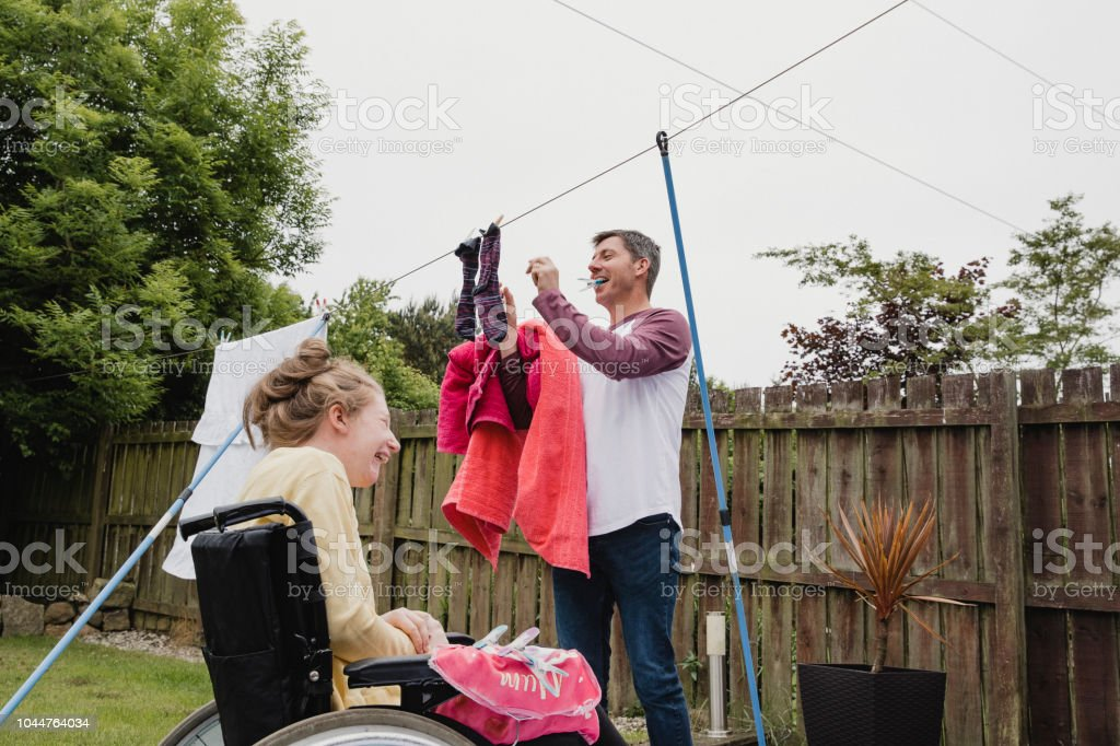 Multitasking Dad Doing Chores with Disabled Daughter stock photo