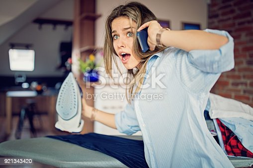 istock Multitasking girl is using mobile phone forget about her iron 921343420