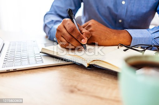 Close up of a black man hands writing reminder on paper agenda on a desk at home