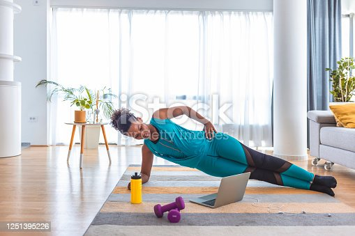 Beautiful woman doing fitness exercise at home while looking at laptop.