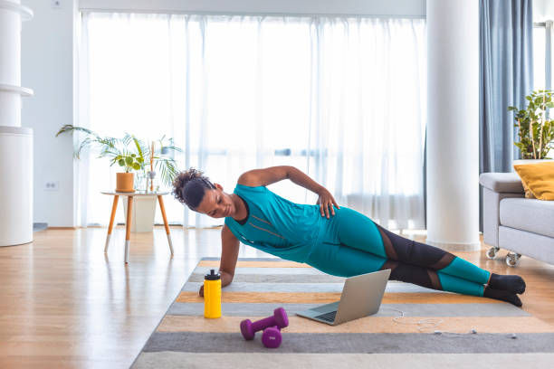 Multitasking is the easiest thing I've ever done Beautiful woman doing fitness exercise at home while looking at laptop. one mid adult woman only stock pictures, royalty-free photos & images