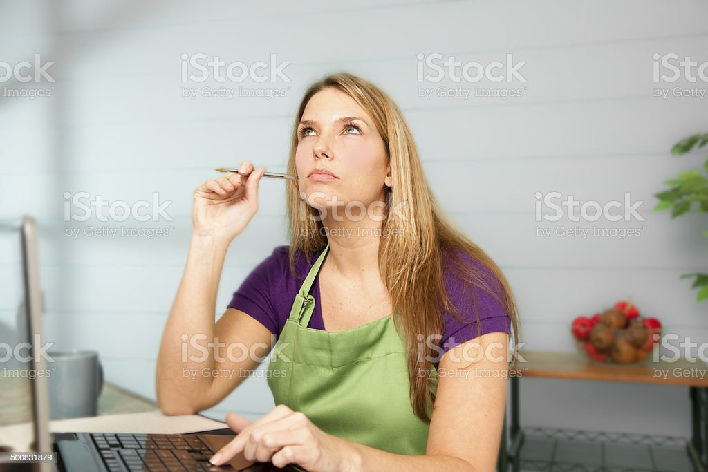 Multi-tasking mom checks internet while cooking dinner.  Kitchen. stock photo
