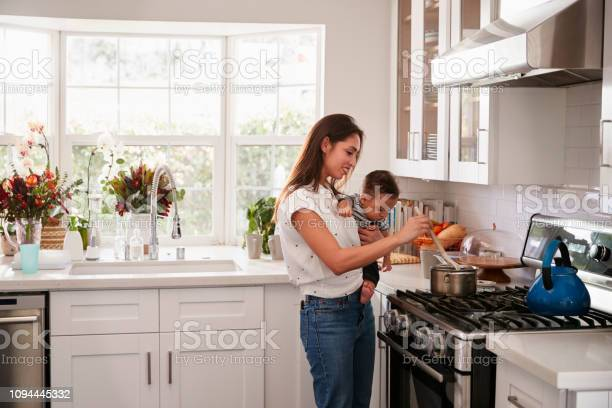 Multitasking mum holding her young baby while she makes food at the picture id1094445332?b=1&k=6&m=1094445332&s=612x612&h=u 4ovr4xnbpyjf f21rxcxpgtmyf6aqonwl7wgxinua=