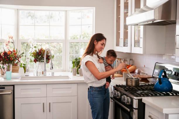 Multitasking mum holding her young baby while she makes food at the picture id1094445332?b=1&k=6&m=1094445332&s=612x612&w=0&h=tis0lltg77armsnpfhlvdiyn2z1axrgkerxlmzugshw=