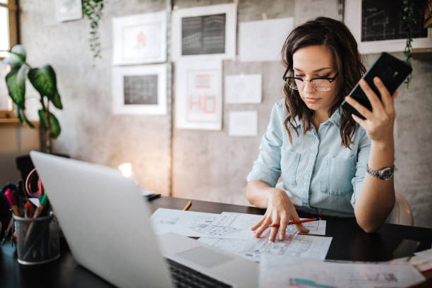 Multitasking of young female entrepreneur at work Young female entrepreneur using smart phone at modern working place entrepreneur stock pictures, royalty-free photos & images
