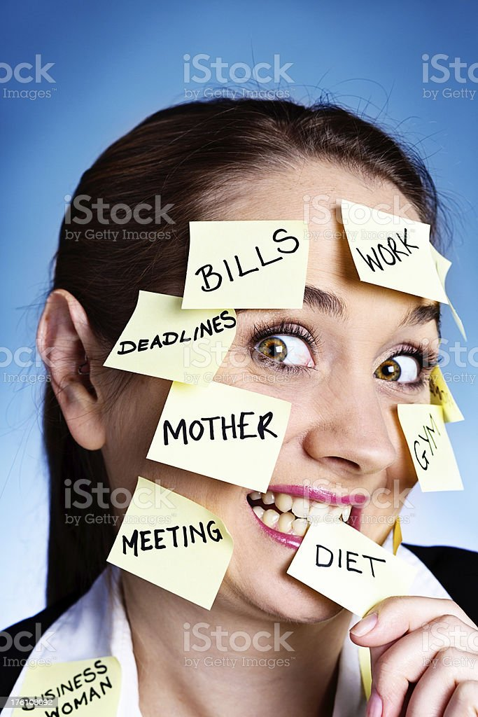 Multitasking woman bites adhesive note labeled DIET; she's losing control! royalty-free stock photo