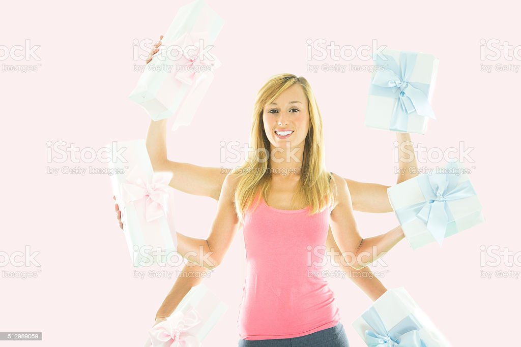 Multi-tasking woman holding many gift/ pink and blue stock photo