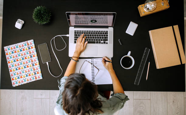 Multitasking young female entrepreneur at home office stock photo