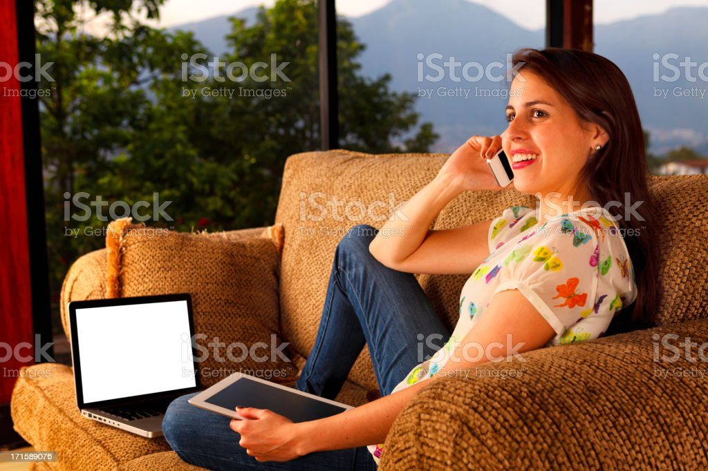 Multitasking young woman talking on couch with tablet and laptop royalty-free stock photo