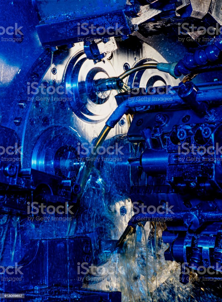 Multi-tool CNC milling machine with jets of oil with blue light stock photo