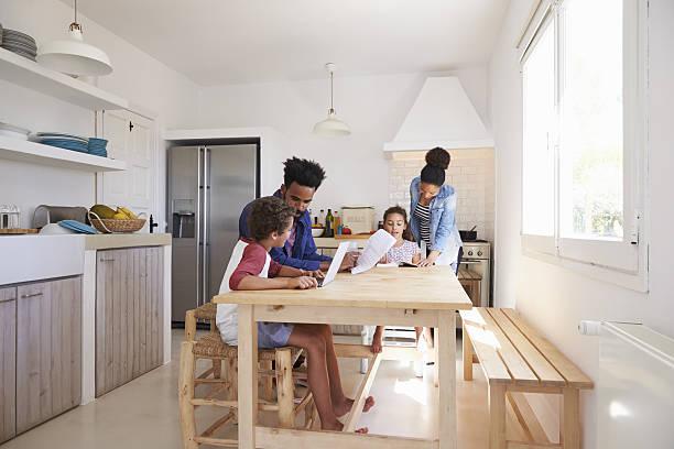 mum and dad help their kids with homework at kitchen - küche aus paletten stock-fotos und bilder
