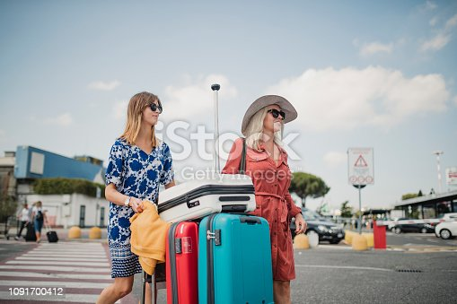 Mother and daughter are walking trough the airport parking lot after arriving in Pisa. They are pushing a luggage cart and taking in their surroundings.