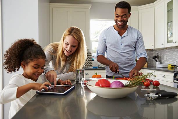 mutter und tochter mit tabletcomputer und vater bereitet speisen - küche aus paletten stock-fotos und bilder