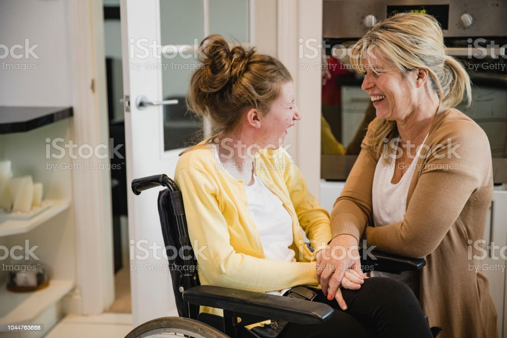 Mum and Disabled Daughter in Kitchen stock photo