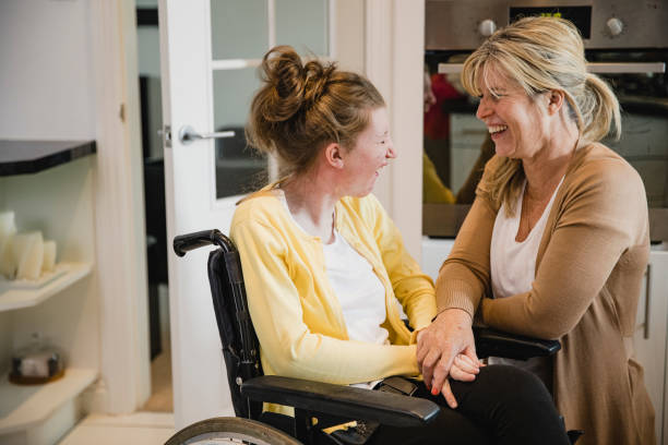 Mum and Disabled Daughter in Kitchen Mature mother is relaxing in the kitchen with her daughter who is in a wheelchair. amyotrophic lateral sclerosis stock pictures, royalty-free photos & images