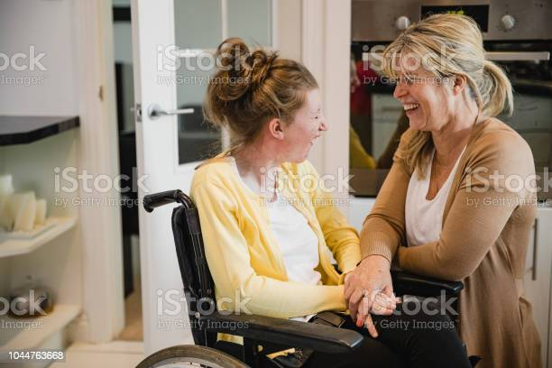Mum And Disabled Daughter In Kitchen - Fotografias de stock e mais imagens de 16-17 Anos