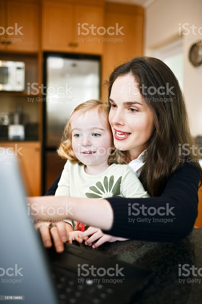 Mum and little daughter look at a computer together royalty-free stock photo